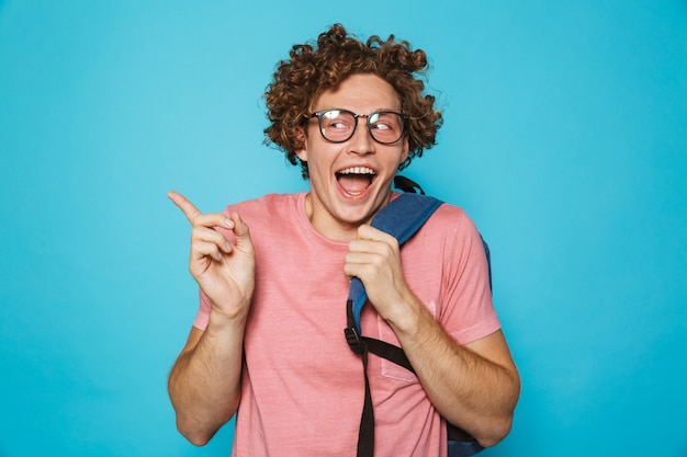 メガネとバックパックを笑顔で身振りで示す巻き毛の流行に敏感なオタク男