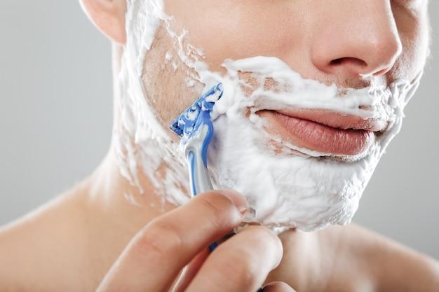 Крупным планом портрет человека с пеной для бритья на лице