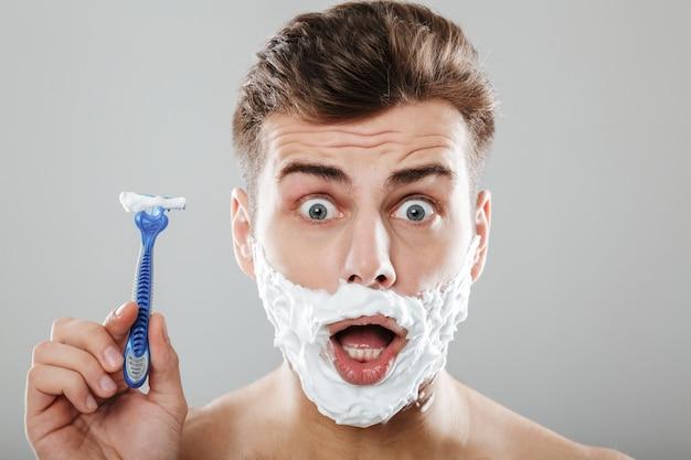 Крупным планом портрет возбужденного человека с пеной для бритья