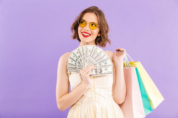 興奮して幸せな女は買い物袋とお金を持って分離されました。