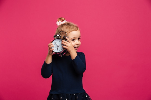 Заинтригованная молодая блондинка держит будильник над розовой стеной
