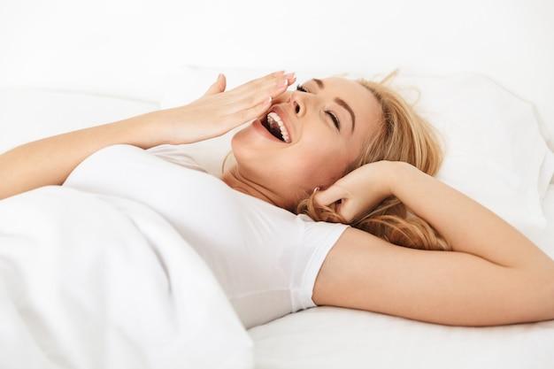Крупным планом счастливой молодой женщины зевая