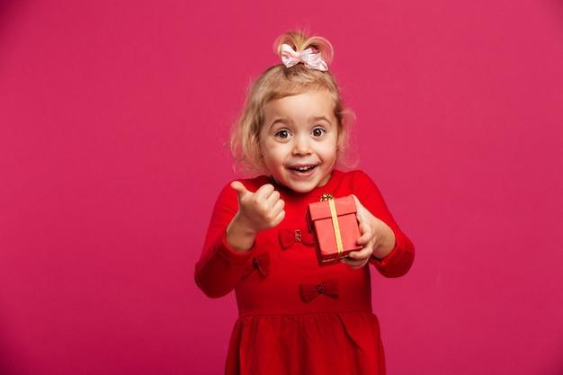 Веселая молодая блондинка в красном платье держит подарочную коробку