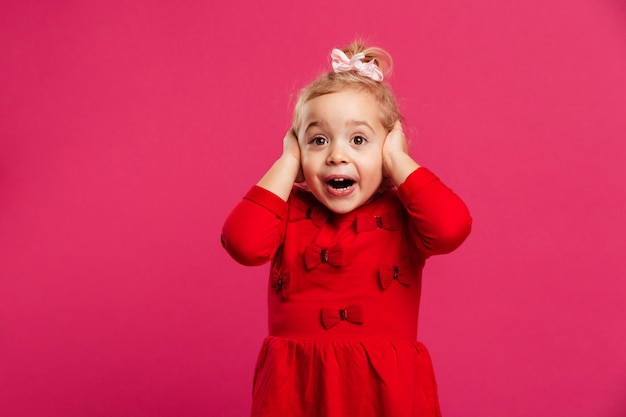 Шокирован счастливым молодая девушка в красном платье, держа ее голову