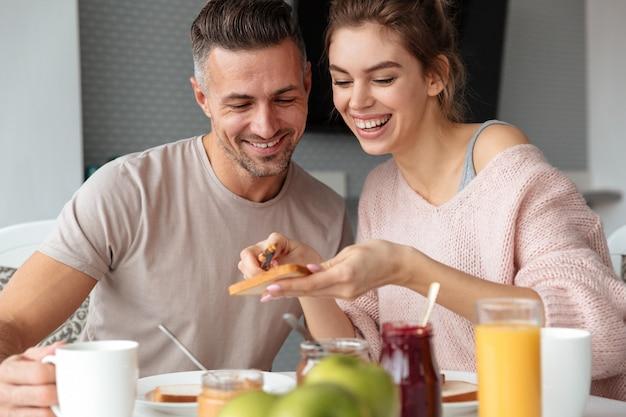 朝食を食べて笑顔の愛情のあるカップルの肖像画