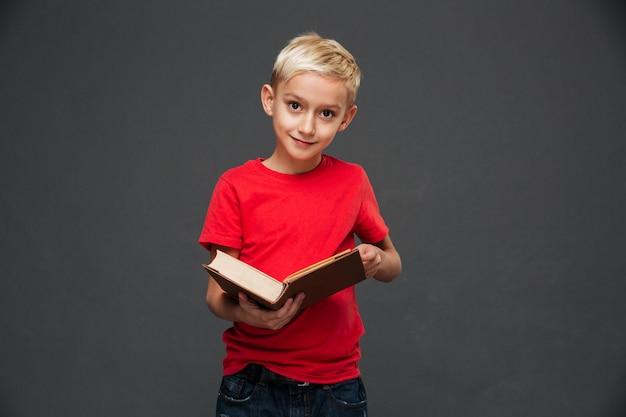 Сконцентрированный маленький мальчик держа книгу.