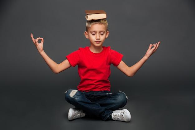 Маленький мальчик медитировать с книгой на голове.