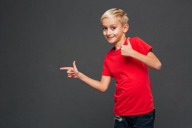 Жизнерадостный ребенок маленького мальчика указывая показывающ большие пальцы руки вверх.