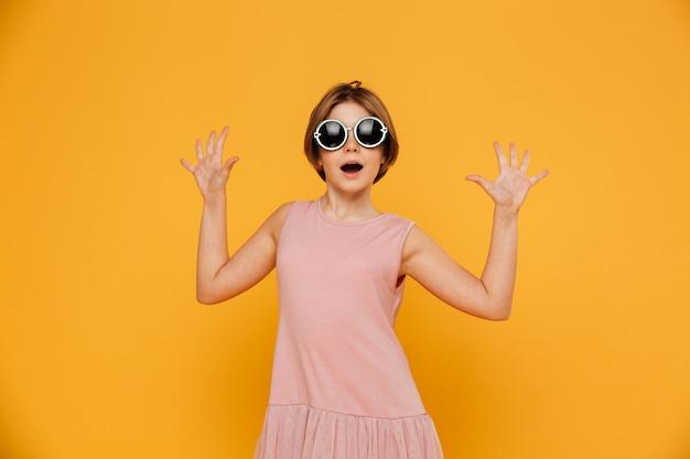 Удивленная девушка с поднятыми руками смотрит в камеру