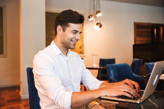 ラップトップに取り組んでいる若い正式な服を着た男の笑顔