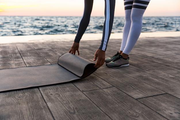 Молодая женщина разворачивается фитнес мат
