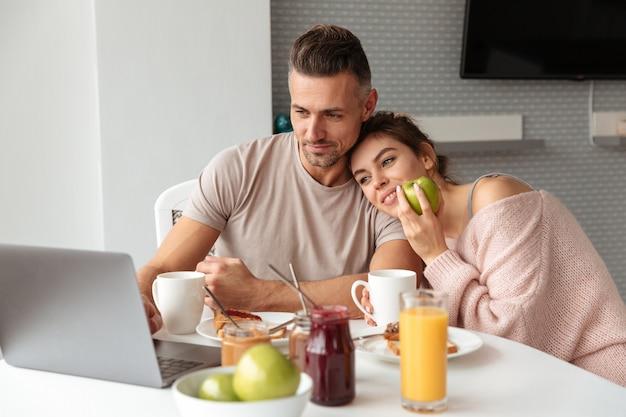 テーブルのそばに座って、キッチンでラップトップコンピューターを使用しながら朝食を食べて満足している愛情のあるカップル