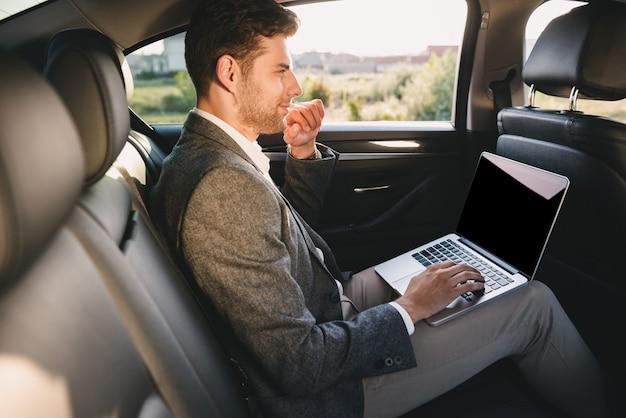 Портрет красавец в костюме работает на ноутбуке, а сзади сидит в автомобиле бизнес класса