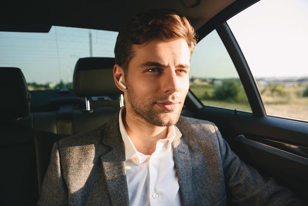 Портрет красивого делового человека в костюме и наушнике сзади сидит во время езды в автомобиле