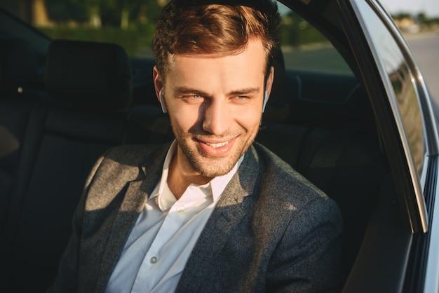 Портрет счастливого взрослого человека, одетого в деловой костюм и наушник сзади, сидя, когда едет в машине