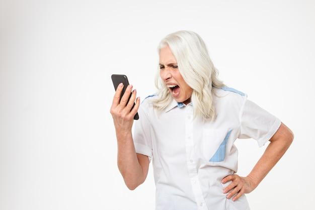 Портрет сумасшедшей зрелой женщины кричать на мобильный телефон