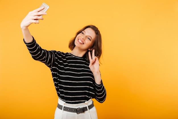 Портрет улыбающейся девушки, делающей селфи