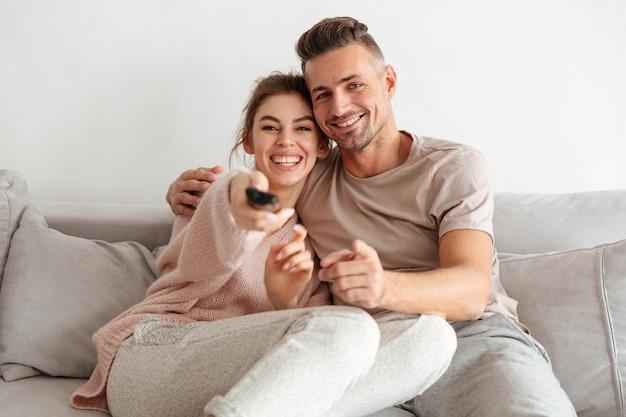 Веселая влюбленная пара вместе сидеть на диване и смотреть телевизор