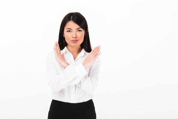 Портрет серьезной азиатской коммерсантки показывая стоп