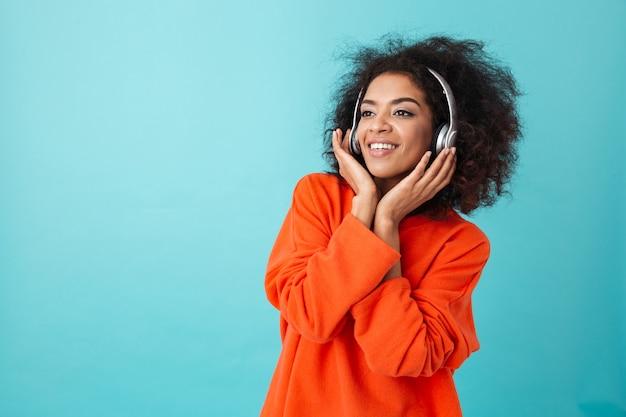 Радостная американская женщина в оранжевой рубашке наслаждается музыкой через беспроводные наушники, слушая любимую мелодию, изолированную над синей стеной