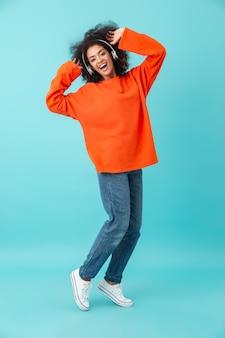Полная длина многоцветная фотография довольной женщины в повседневных джинсах, слушающей музыку через беспроводные наушники, изолированная на синей стене