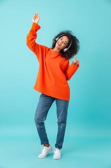 Полная длина многоцветная фотография довольной женщины в повседневных джинсах, танцующих во время прослушивания музыки с помощью беспроводных наушников, изолированных на синей стене