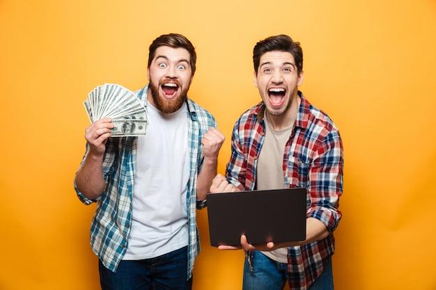 Портрет двух счастливых молодых людей, занимающих портативный компьютер