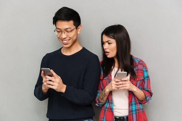 携帯電話でチャット不機嫌な若いアジア女性。