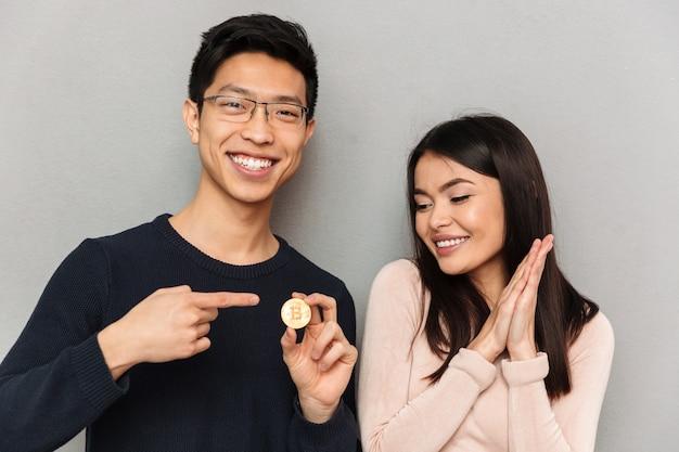 ビットコインを保持している陽気な若いアジアの愛情のあるカップル。