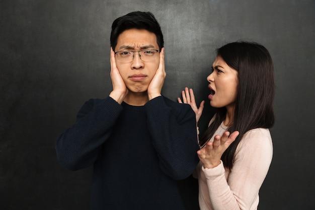 Раздражанный азиатский человек в очках покрывая уши