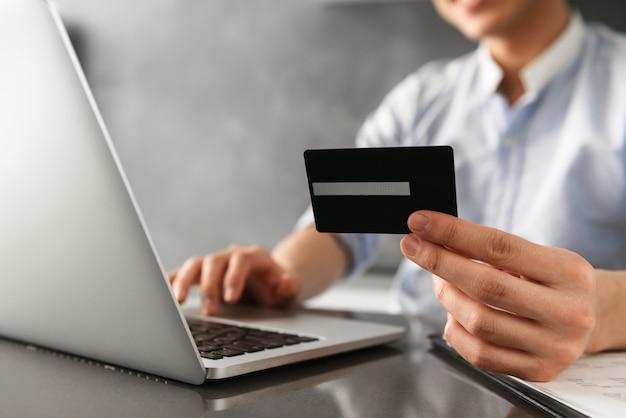 Крупным планом мужчина держит пластиковую кредитную карту