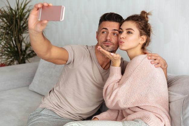 Довольно милая пара сидит на диване и делает селфи на смартфоне дома