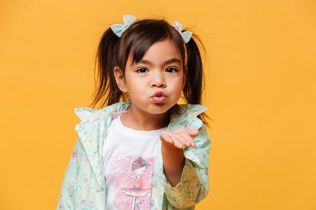 Маленькая девочка дует поцелуи.