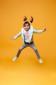 Жизнерадостный ребенок маленькой девочки скача изолированный