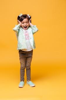 Изображение кричащего эмоционального положения ребенка маленькой девочки изолированного над желтой предпосылкой.