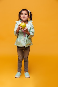 Маленькая девочка ребенок ест яблоко.