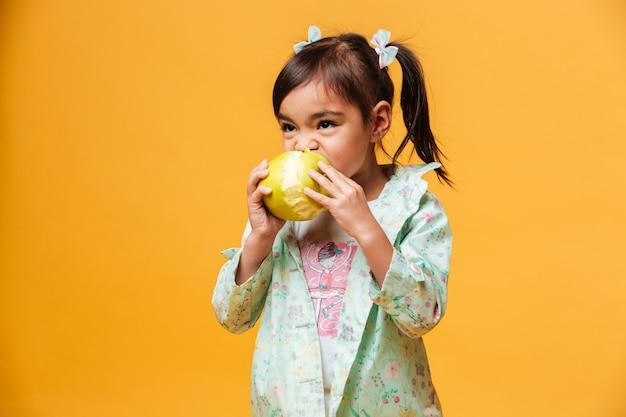 小さな女の子子供食用リンゴ。
