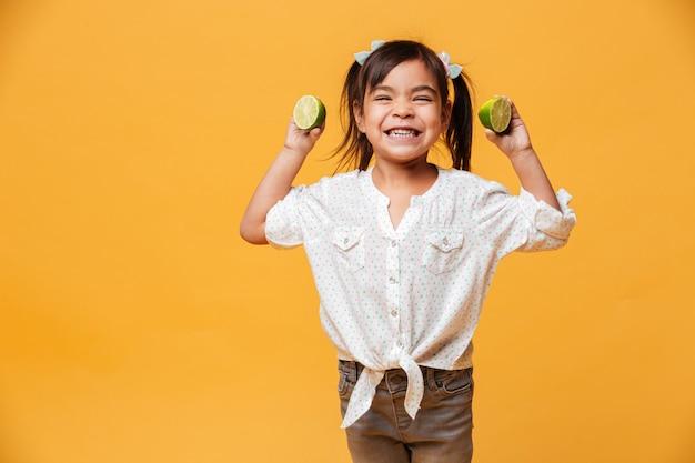 Маленькая девочка ребенок держит лайм.
