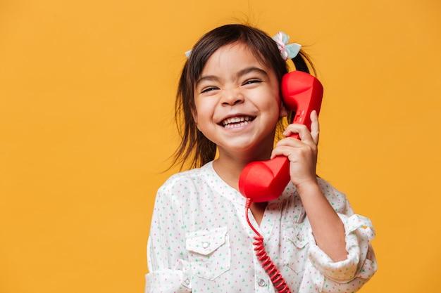 赤いレトロな電話で話している幸せな興奮した少女。