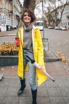 Веселая симпатичная молодая женщина, одетая в резиновые сапоги