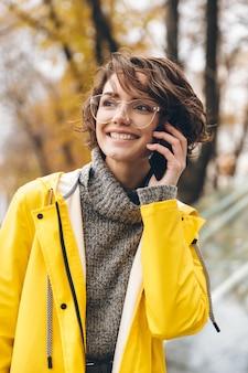 黄色のレインコートとメガネの若い女性のショットは、楽しいモバイル会話を持つ外で過ごす時間