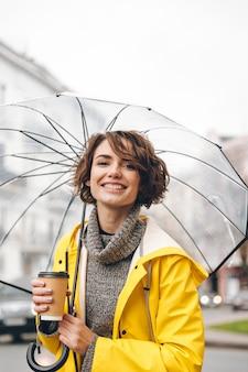 Веселая молодая женщина, одетая в плащ