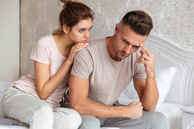 Прекрасная пара, сидя на кровати, а женщина успокаивает своего парня, который расстроен