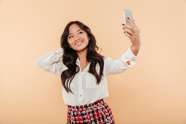 Великолепная азиатская женщина с длинными темными волосами делает селфи фото на своем смартфоне, любуясь на бежевом фоне