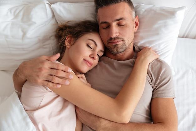 Взгляд сверху довольно любящих пар спать совместно в кровати дома