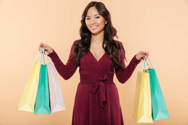 Привлекательная сианская женщина в элегантном темно-бордовом платье покупает и показывает пакеты с покупками на бежевом фоне