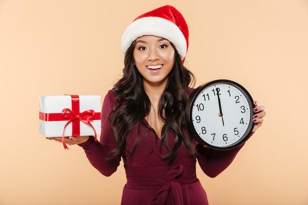 Веселая женщина в красной шапке деда мороза празднует новый год с часами и подарочной коробкой в руках на персиковом фоне