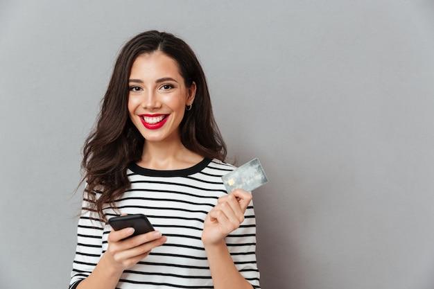 Портрет счастливая девушка держит мобильный телефон