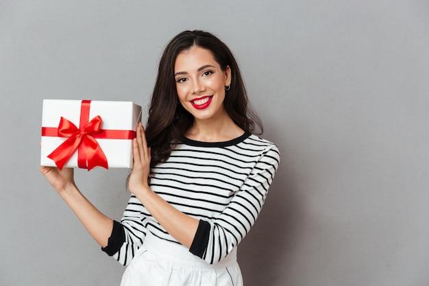 Портрет красивой девушки с подарочной коробкой
