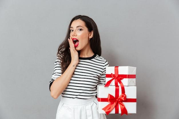Портрет удивленной женщины, держащей стопку подарочных коробок